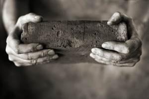 Sepia toned photo of DIrty hands holding an old brick
